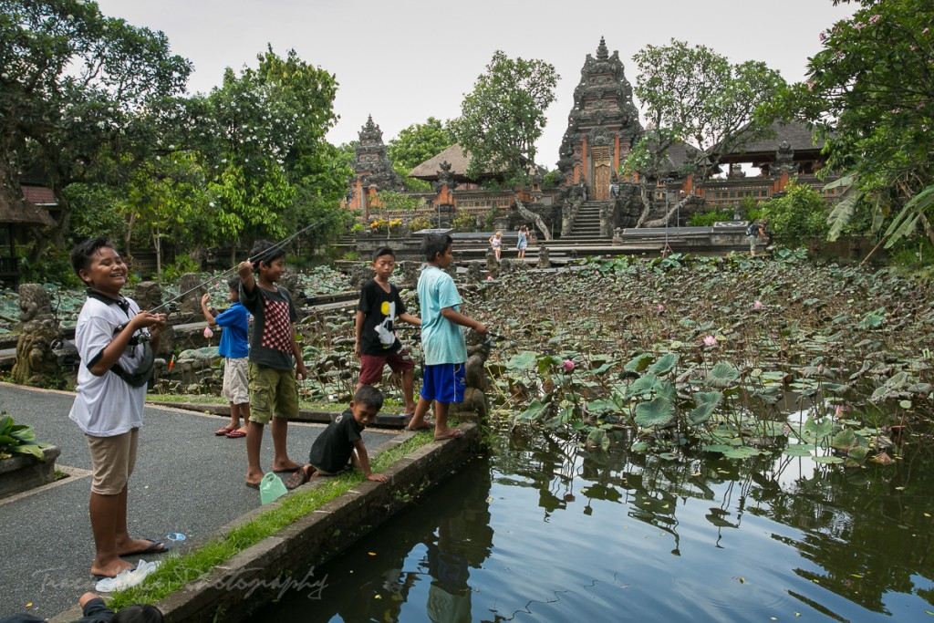 Boys fishing at Pura Taman Saraswati temple.