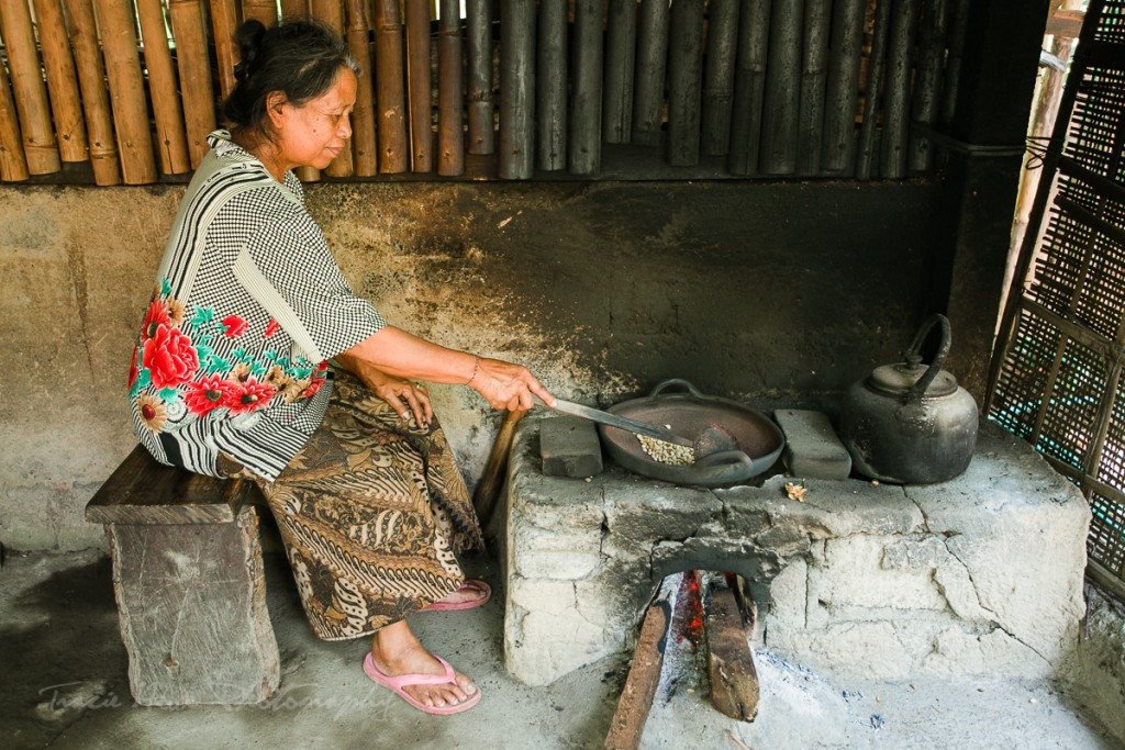 A woman hand roasting coffee beans.