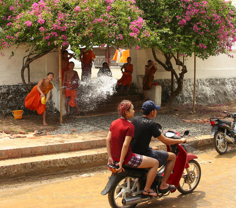 A moment before a monk throws water on a passing scooter